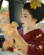 Entertainers Photo Prints - A Kimono-clad Geisha Applies Lipstick Print by Justin Guariglia