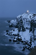 Nautical Structures Photos - A Lighthouse Atop Snow-covered Cliffs by Tim Laman