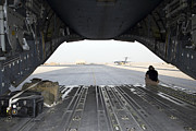 Airfield Prints - A Loadmaster Sits On The Rear Ramp Print by Terry Moore