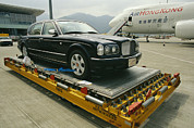 Commercial Structures Framed Prints - A Luxury Bentley Unloaded From An Framed Print by Justin Guariglia