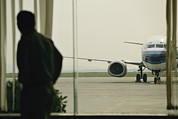 Southern Province Photos - A Man At A Chinese Airport Walks by Justin Guariglia