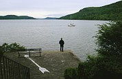 Otsego Lake Posters - A Man Looks Out At A Sailboat Anchored Poster by Raymond Gehman