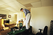 Hardware Posters - A Man Plays Golf On His Desk Poster by Joel Sartore