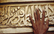 Religious Art Photos - A Man Runs His Hand Over Arabic Script by Justin Guariglia