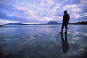 Silhouettes Metal Prints - A Man Stands At The Tide-line On Vargas Metal Print by Joel Sartore