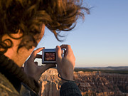 Digital Camera Prints - A Man Takes A Picture In Bryce Canyon Print by John Burcham