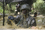 Trudging Posters - A Marine Splashes As He Makes His Way Poster by Stocktrek Images