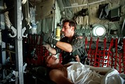 Candid Portraits Prints - A Medic Adjusts The Intravenous Drip Print by Everett