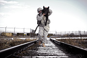 Railroad Tracks Framed Prints - A Military Dog Handler Uses An Framed Print by Stocktrek Images
