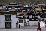 Tibetan Buddhism Framed Prints - A Monk Walks Past A Small Village Framed Print by Jimmy Chin