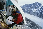 Snow Scenes Prints - A Mountain Climber Reads Print by Gordon Wiltsie