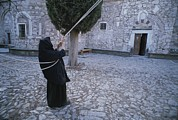 Ropes Framed Prints - A Nun Pulls On Ropes In A Courtyard Framed Print by Tino Soriano