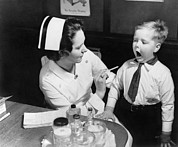 Candid Portraits Photo Prints - A Nurse Examining The Teeth Of A Boy Print by Everett