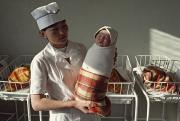 Humans Posters - A Nurse Holds A Tightly Wrapped Newborn Poster by Dean Conger