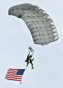 Flags Flying Prints - A Parachutist Flies The American Flag Print by Stocktrek Images