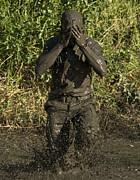 Obscured Face Art - A Participant Wipes Mud From His Face by Stocktrek Images