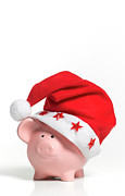 Piggy Bank Framed Prints - A Piggy Bank Wearing A Santa Hat Framed Print by Peter Dazeley