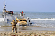 Beachhead Posters - A Sailor Directs A Humvee Poster by Stocktrek Images