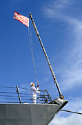 First Navy Jack Prints - A Sailor Lowers The U.s. Navy Jack Print by Stocktrek Images