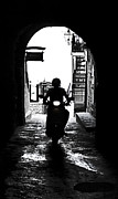 Lane Prints - a scooter rider in the back light in a narrow street in Italy Print by Joana Kruse