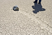 Dry Lake Photos - A sliding rock and man on The Racetrack Playa by Ed Book