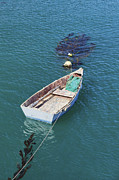 Small Boat Prints - A Small Dinghy Floats On Its Mooring Print by Douglas Orton
