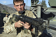 M16 Posters - A Soldier Displays His M16 A4 Rifle Poster by Stocktrek Images