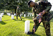 Headstones Prints - A Soldier Places A Flag In Front Print by Stocktrek Images