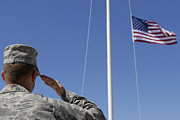 Soldier Photos - A Soldier Salutes The American Flag by Stocktrek Images