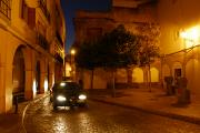 Night Scenes Photos - A Street Scene With A Car At Night by Raul Touzon