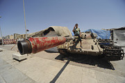 Muammar Gaddafi Prints - A T-55 Tank With Two Children Playing Print by Andrew Chittock