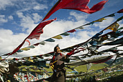 Tibet Framed Prints - A Tibetan Pilgrim Hoists Prayer Flags Framed Print by Justin Guariglia
