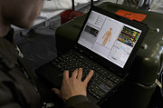 Laptop Framed Prints - A U.s. Airman Looks At A Laptop To Help Framed Print by Stocktrek Images