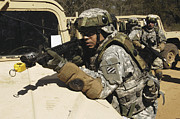 Hmmwv Posters - A U.s. Army Soldier Pulls Security Poster by Stocktrek Images