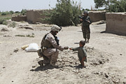 Kneeling Prints - A U.s. Marine Gives Candy To An Afghan Print by Stocktrek Images