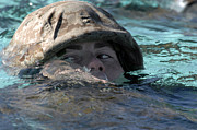 Helmet  Prints - A U.s. Marine Swims Across A Training Print by Stocktrek Images