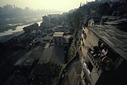 Peoples Republic Of China Photos - A Woman Hangs Laundry In Of The Houses by Justin Guariglia