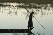 Full-length Portrait Art - A Woman Stands At The End Of A Rowboat by Lynn Abercrombie