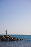 Sete Photos - A Woman Stands On A Breakwater by Taylor S. Kennedy