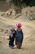 Dirt Roads Photo Prints - A Yemeni Woman And Child Carrying Print by Michael Melford