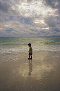 Alejandro Prints - A Young Boy Walks Along A Beach Print by Raul Touzon