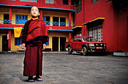 Red Robe Posters - A young Buddhist monk stands on the square in front of the monas Poster by Max Drukpa