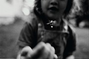 Innocence Photo Framed Prints - A Young Girl Reaches Out For A Firefly Framed Print by Stephen Alvarez