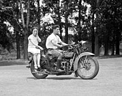 1920s Art - A Young Man Drives A  Motorcycle While by Everett