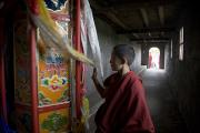 Buddhist Clothing Prints - A Young Monk Spinning A Prayer Wheel Print by David Evans