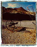 Wagon Wheels Photos - Abandoned wagon wheels in the desert by Geoffrey Wallace