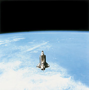 Space Shuttle Photo Prints - Aerial View Of The Space Shuttle In Orbit Above Earth Print by Stockbyte