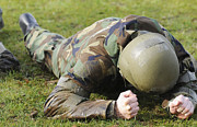 Military Training Posters - Airman Crawls Through A Wet Field Poster by Stocktrek Images