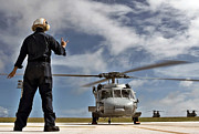 Gesturing Posters - Airman Signals The Pilot Of An Mh-60s Poster by Stocktrek Images