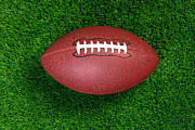 Sport Equipment Prints - American football on grass Print by Richard Thomas